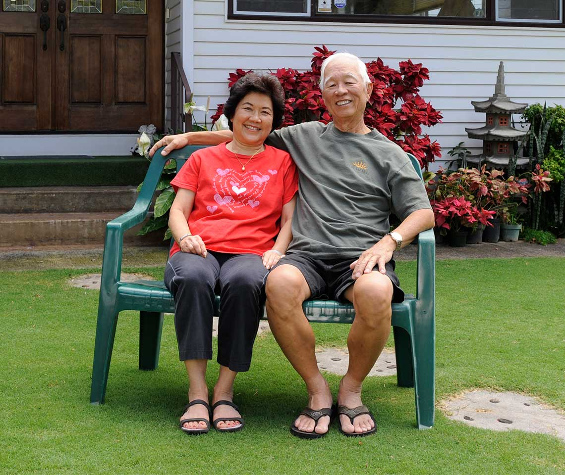 An-older-couple-sitting-in-front-of-a-house-in-Hawaii