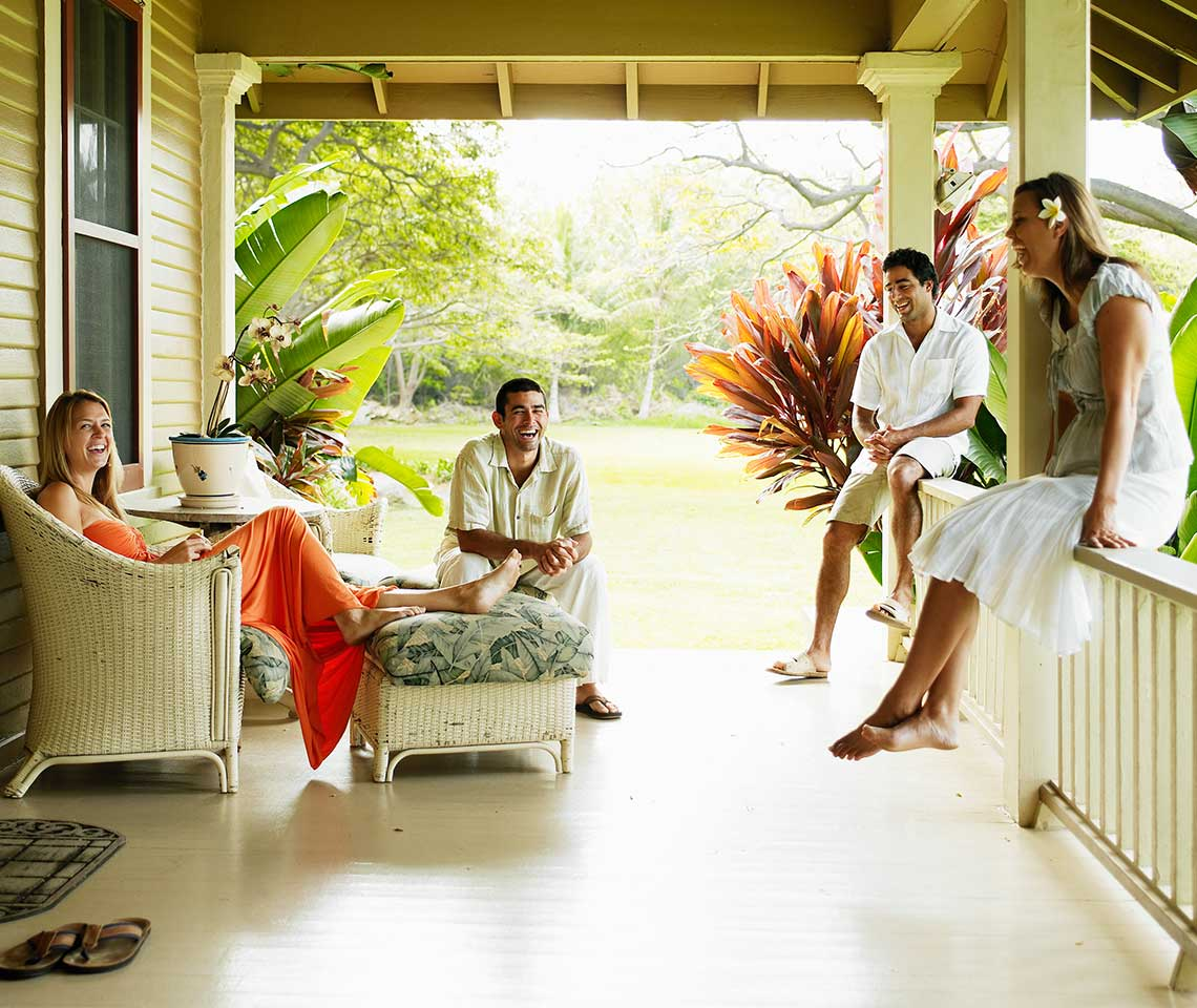Four-people-laughing-on-a-porch-in-Hawaii